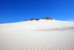 Sand dunes on the desert. Sand dunes on the white sand desert with green hill on the blue sky backround in poland Royalty Free Stock Photos