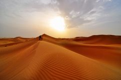 Sand dunes in desert. Lone man standing in the desert sand dunes Royalty Free Stock Photo