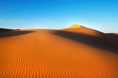 Sand dunes in the desert , warm dry sand under blue sky. Nature Stock Photography