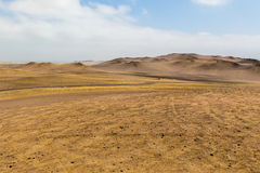 Sand dunes of different sizes and a dirt road Royalty Free Stock Photo
