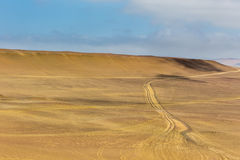 Sand dunes of different sizes with traces of car wheels in the Paracas Reserve Desert Stock Image