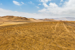 Sand dunes of different sizes with traces of car wheels Stock Image