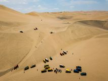 Sand dunes with dune buggies. Sand dunes with buggy cars aerial panorama in Hucachina Peru desert vehicle tourist attraction transport big wheels south america stock photo