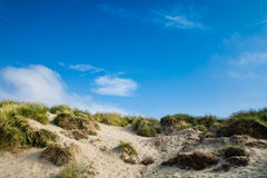 Sand dunes with grass and blue skies, Camber Sands. Beautiful dunes and grass with blue sky - Camber Sands, East Sussex, England Stock Image