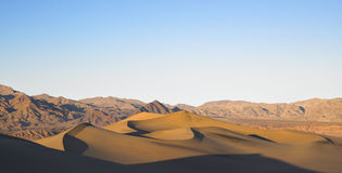 Sand Dunes with Mountains in Background Stock Photo