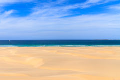 Sand dunes near to the ocean with cloudy blue sky, Boavista, Cap Royalty Free Stock Images