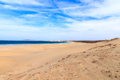 Sand dunes near to the ocean with cloudy blue sky, Boavista, Cap Royalty Free Stock Photography