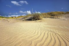 Sand dunes and ocean at sunset Stock Photography