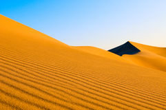 Sand dunes over blue sky Stock Image