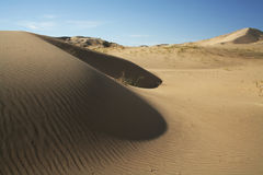 Sand dunes with ripples. Sand dunes ripple in the desert with blue skies and a few clouds in the background Stock Photo