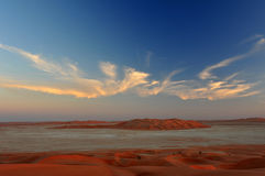 Sand dunes in Rub al Khali desert. Sandy dunes in desert Rub al Khali in Sultanate Oman with white clouds and blue sky at sundown Royalty Free Stock Photos
