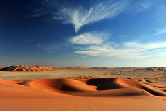 Sand dunes in Rub al Khali desert. Sandy dunes in desert Rub al Khali in Sultanate Oman with white clouds and blue sky at sundown Royalty Free Stock Image