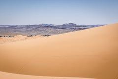Sand dunes of Sahara. Sand dunes and Black desert of Sahara near Merzouga, Morocco Stock Photo