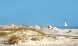 Sand Dunes and Sailboat. Oceanside sand dunes with sailboat in distance on calm seas Royalty Free Stock Photo