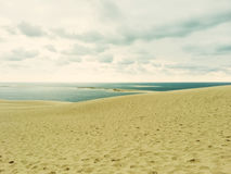 Sand dunes, sea and cloudy sky Stock Photography