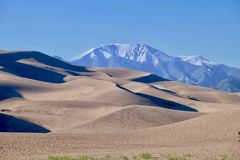 Sand dunes and snowy mountains at the background. Royalty Free Stock Images