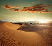 Sand dunes at sunset light on background of dramatic sky Stock Photo