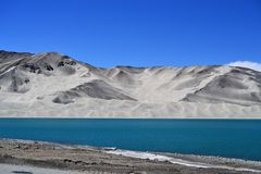 Sand dunes and turquoise blue water at Bulunkou lake on Karakoram Highway, Xinjiang royalty free stock photos