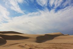 Sand dunes with tyre tracks. Desolate sand dunes with tyre tracks on sunny day Royalty Free Stock Photography
