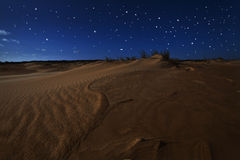 Sand dunes under full moon light and stars Stock Photography