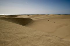 Sand dunes with walking people and ocean behind Royalty Free Stock Image
