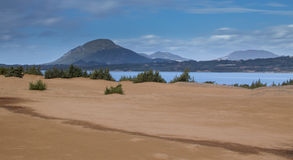 Sand dunes and wild bushes and a mountain on the background. Issos Beach ,Korission Lake ,Corfu Greece Europe Stock Image
