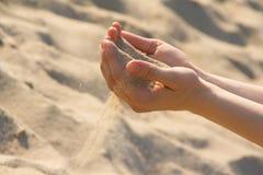 Sand durch Finger Stockbild