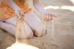 Sand durch seine Finger Stockfoto