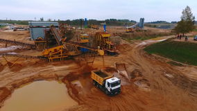 Sand extraction at quarry. Mining conveyor pour sand in dumper truck. Sand extraction at quarry. Sky view of mining equipment working at industrial area. Mining stock video footage