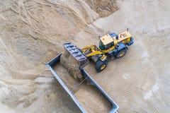 Sand för hjulladdarpäfyllning på dumper arkivbild