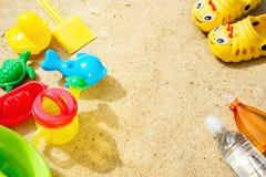 Sand för strandsommarsolen lurar leksak- och för flaskvatten häftklammermatare och Sunscreen Royaltyfri Bild