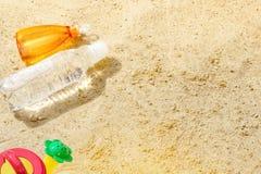 Sand för strandsommarsolen lurar leksak- och för flaskvatten häftklammermatare och Sunscreen Arkivbilder