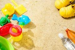 Sand för strandsommarsolen lurar leksak- och för flaskvatten häftklammermatare och Sunscreen Royaltyfria Foton