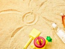 Sand för strandsommarsolen lurar leksak- och för flaskvatten häftklammermatare och Sunscreen Arkivfoto
