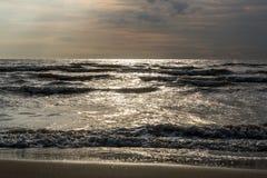 Sand för washes för havsvatten på stranden på en solig dag royaltyfri foto