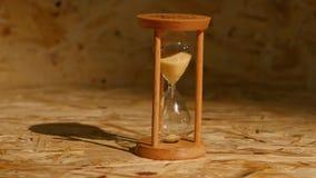 Sand faller snabbt till och med ett timglas arkivfilmer