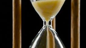 Sand faller till och med en flaskhals i ett timglas _ close upp lager videofilmer