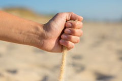 Sand falling from the fist Royalty Free Stock Photo