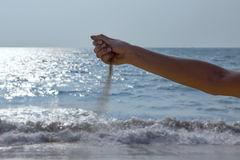 Sand falling from a hand. At the seachore royalty free stock images