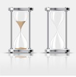 Sand falling in the hourglass on dark background Royalty Free Stock Image