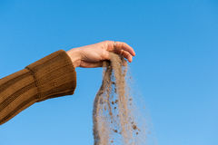 Sand falling from the woman's hand stock images