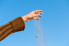Sand falling from the woman's hand Stock Photo