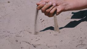 Sand falls from a man s hand on the beach in slow motion. Dirty sand in hand of men