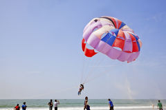 Sand flies as Paraglider takes off stock photo