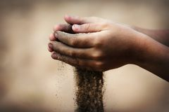 Sand flowing through the hands of the child. The concept of life and death royalty free stock photography