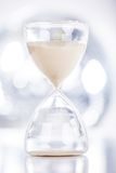 Sand flowing through an hourglass. Close View Of Sand Flowing Through An Hourglass Stock Images