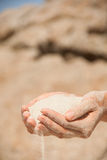 Sand flows through the female hands Stock Photography