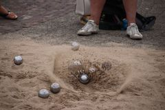 Sand is flying away when ball is landing on the ground during boules game royalty free stock images