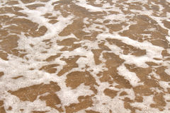 Sand, foam and water background texture Stock Images