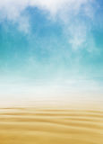 Sand and Fog. A long exposure of flowing ocean water over sand disappearing into the horizon with swirling fog above.  Image displays a soft yellow to blue Royalty Free Stock Photo